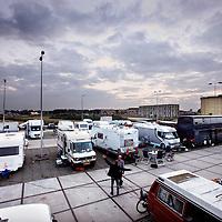 Nederland, Amsterdam , 1 oktober 2014.<br /> De rij caravans met mensen die een zelfbouwkavel willen kopen op het Zeeburgereiland wordt steeds groter.<br /> Sommige staan al een paar weken in de wachtrij totdat ze een kavel mogen kopen. Pas volgende week zaterdag gaan de kavels pas in de verkoop, maar wie weg gaat, verliest zijn plek in de rij.<br /> Een van de kampeerders staat er al een tijdje in zijn caravan: 'Ik ben hier behoorlijk vroeg gaan staan, want er is &eacute;&eacute;n kavel waar ik echt ge&iuml;ntresseerd in ben. Er hoeft er maar een eerder te zijn en dan ben je 'm kwijt.'<br /> De wachtende kopers vinden het best gezellig op het terrein: 'Je ontmoet een soort van je toekomstige buren als het zo doorgaat. Dat geeft een apart campinggevoel en we barbecuen samen.'<br /> Een probleempje, als je weggaat ben je je plek kwijt. 'Als je moet werken moet je zorgen dat er iemand anders op je plek zit. Ik had hier eerst helemaal geen zin in, maar het is toch wel een bizar avontuur.'<br /> Foto:Jean-Pierre Jans