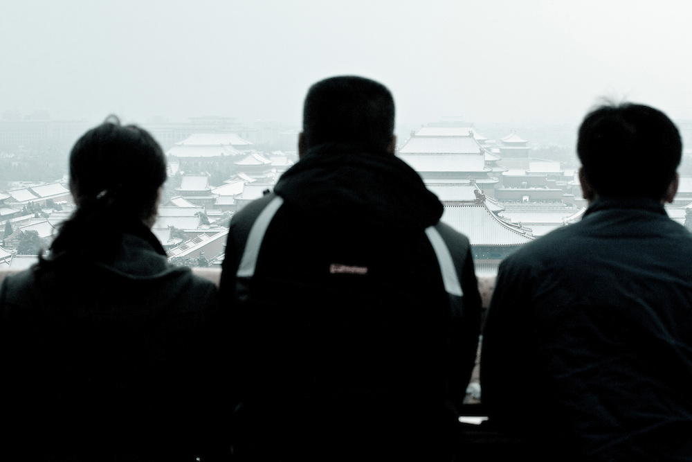 Beijingers and tourists are looking at the Forbidden city under snow from the Coal Hill (Jingshan park), feb. 13  after a snowfall that local authorities say they have artifically provoked to fight the exceptional drought in northern China. Snowfalls of feb. 10 and 13 were the latest in winter since 60 years.