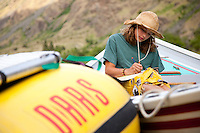 Young woman writing in journal while rafting Hell's Canyon of the Snake River, ID / OR. Hell's Canyon is the deepest canyon in North America.