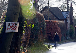 © Licensed to London News Pictures. 27/01/2012. Hyde Heath, UK. A woman walks her dog past an anti HS2 (High Speed Rail 2) sign outside a property in the village of Hyde Heath, Buckinghamshire. Scheduled to be completed by 2033, the new Rail system will have huge effects on the English village. Photo credit : Ben Cawthra/LNP