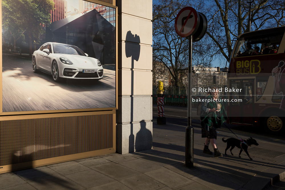 A lady walks her dog alongside a Porsche luxury car ad where a new dealership is due to open on the corner of Clarges Street, and Piccadilly, W1, on 20th January 2020, in London, England.