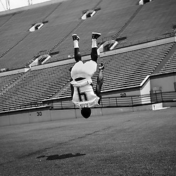 Virginia Tech football player, David Wilson, is caught in midair while doing a series of eight consecutive backflips while clowning around at media day at Lane Stadium. Wilson, a freshman highly touted for his athleticism ran the fastest freshman 40 yard dash time this spring, 4.33 seconds, in addition to benching 315 pounds and squatting 605 pounds. ***Note, Jersy name is wrong,...player jersey says Clark, but player is David Wilson.<br /> <br />  -- Virginia Tech has been consistently winning each season unlike former ACC powerhouses Miami and Florida State. They led the conference with a 10-4 record.  --
