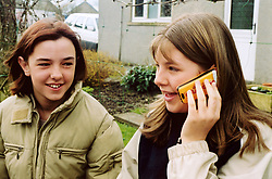 Two teenage girls using mobile phones UK