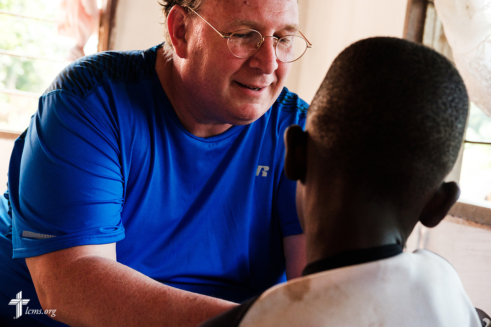 The Rev. Michael Awe, team leader and pastor at Hope Lutheran Church, South Sioux City, Neb., takes vitals from a young patient on the second day of the LCMS Mercy Medical Team on Tuesday, May 8, 2018, in the Yardu village outside Koidu, Sierra Leone, West Africa. LCMS Communications/Erik M. Lunsford