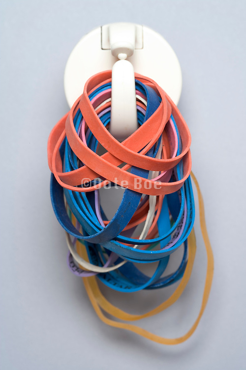 group multi colored rubber bands hanging from a kitchen towel clip