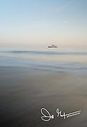 A ship at sunrise along the coast of Santiago island, Galapagos islands, Ecuador.