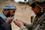 Private Dan Burris, right, of the 82nd Airborne gives a cigarette to an Afghan villager in Kshahah Lakhchack after searching his home in Kandahar province, Afghanistan on Monday, March 26, 2007.