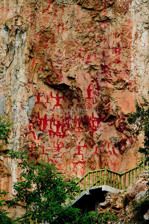 Appreciation for the size and scale of the Huashan ancient rock paintings can be had when taking into account the walkway and trees.