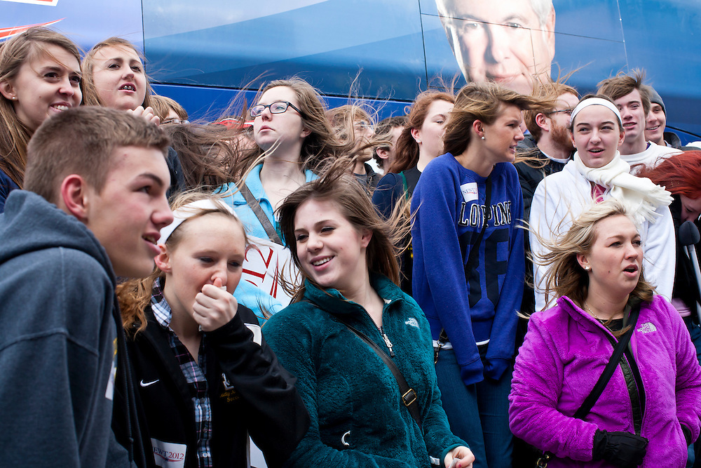 Students fight a strong wind as they pose for a group photo in front of the campaign bus of Republican presidential candidate Newt Gingrich outside the West Towne Pub on Sunday, January 1, 2012 in Ames, IA.