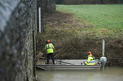 © London News Pictures. 30/12/2013. Yalding, UK.  Members of the Environment Agency use a boat to debris from the banks of the river Medway at Yalding in Kent, an area previously hit by flooding. The UK is braced for more bad weather after heavy rainfall caused flooding in parts last week.  . Photo credit : Ben Cawthra/LNP
