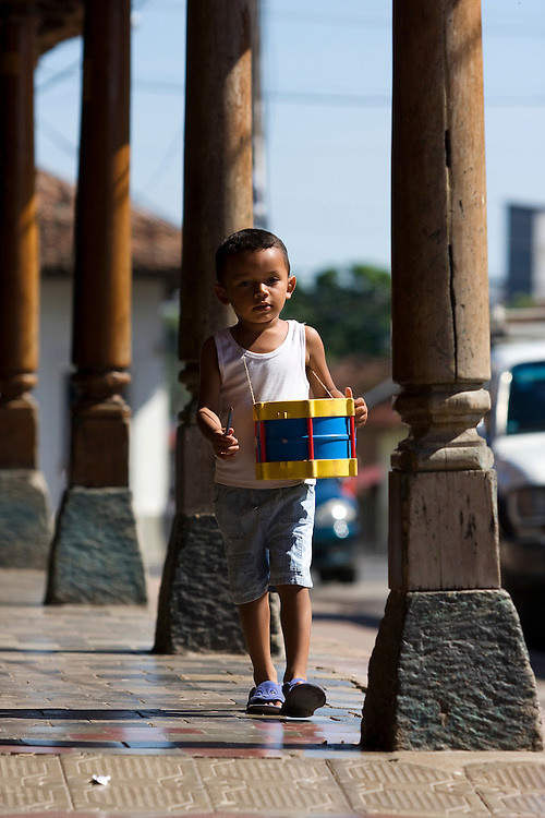 A child with a brightly colored drum walks through the wooden pillars in colonial Nicaragua.
