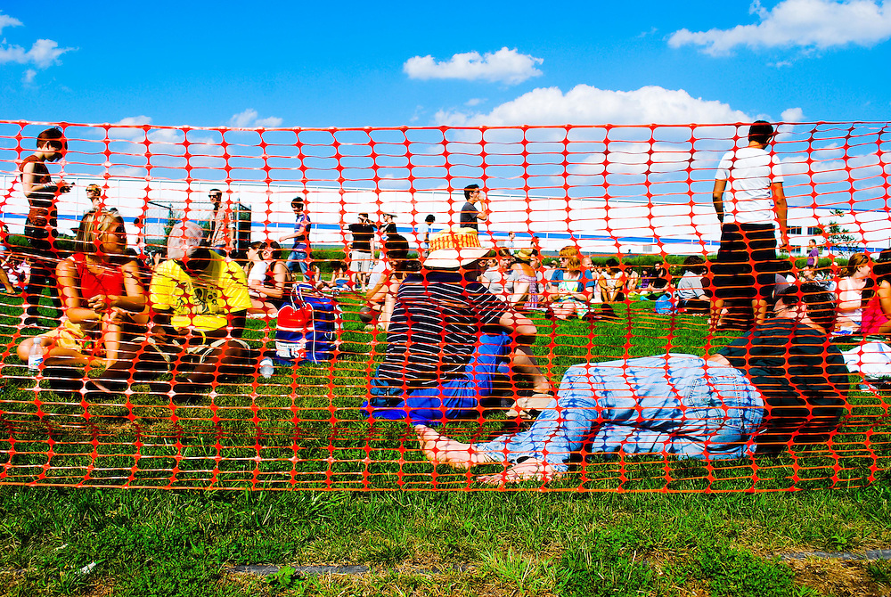 Pool partiers lounge in the grass behind orange fencing at the JELLY Pool Party free concert series East River State Park, Williamsburg, Brooklyn, New York
