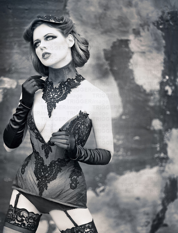 Black and white photo of a beautiful young woman wearing an elaborate corset, hair piece, underwear, garter and stockings while gazing off into the distance