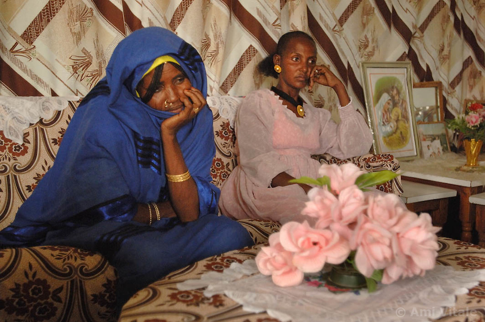 Women from Hamada meet inside the home of Tsion (in pink) as they discuss issues related to the donkey initiative. Also there is Tiblets in white scarf and Kadija in blue in  Barentu, Eritrea at dusk August 30, 2006.     (Photo by Ami Vitale)