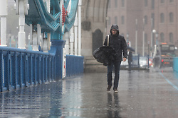 © Licensed to London News Pictures. 26/08/2014. London, UK. A man struggles with his umbrella on Tower Bridge during heavy rain and strong wind. Heavy rain and cold weather are forecast for the rest of the day. Photo credit : Vickie Flores/LNP
