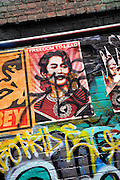 Poster of Nobel Peace Prize recipient Aung San Suu Kyi slowly disappearing beneath the ever-changing graffiti in Hosier Lane, Melbourne, Australia