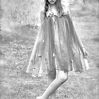 A young girl standing alone outdoors looking at camera wearing a summer dress