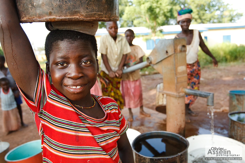 A girl holds a bucket of water on top of her head to carry back home after she filled it from a handpump in the village of Moglaa, Ghana on Thursday November 11, 2010.