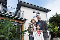 Parents and daughter (7-9) embracing outside new home portrait
