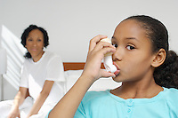 Nurse watching girl (7-9) using inhaler in hospital