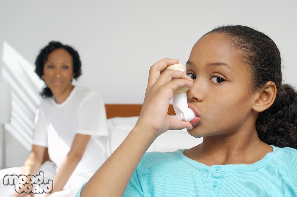 Nurse watching girl (7-9) using inhaler in hospital