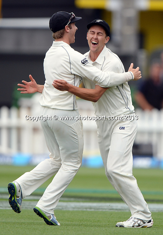 Trent Boult celebrates with Kane Williamson after taking a spectacular catch to dismiss Denesh Ramdin on Day 3 of the 2nd cricket test match of the ANZ Test Series. New Zealand Black Caps v West Indies at The Basin Reserve in Wellington. Friday 13 December 2013. Mandatory Photo Credit: Andrew Cornaga www.Photosport.co.nz