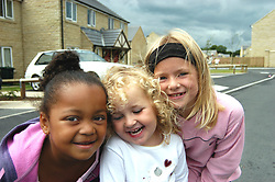 Girls playing in the street outside their Housing Association estate homes; Halifax; Yorkshire UK