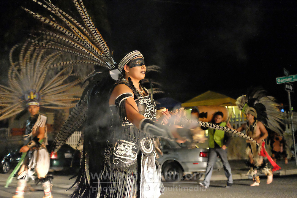 A dancer from Yaocuauhtli blesses waiting cars with copal in the intersection of Pacific and Garner in east Salinas. The ACFA Day of the Dead procession traced a route touching upon the sites of nine shootings.
