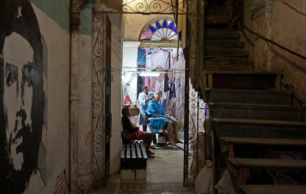 Photographer Mark Evans pops into a local's house in Old Havana, Cuba for a five dollar haircut. <br />