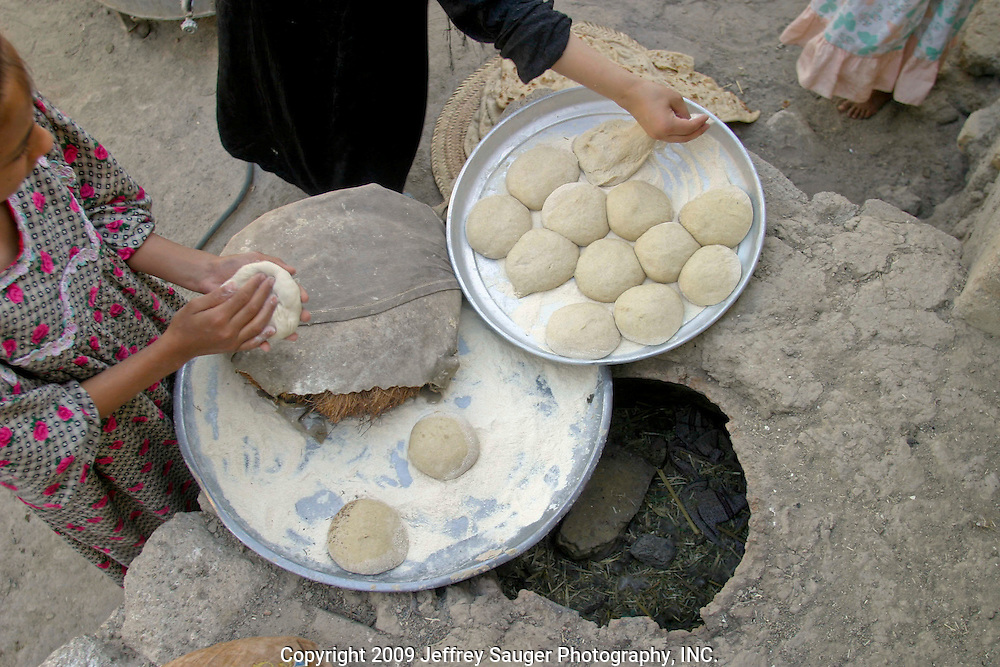 Women and young girls make traditional Iraqi flat bread during the Al-Kasid family's Istikbal, or homecoming, in their home village Suq ash Shuyukh, about 20 miles southeast of Nasiriyah, Iraq, Wednesday, July 30, 2003...The women spend most of their time making dough, baking bread, milking cows, taking care of children, preparing food, etc. as the men gather out front of the compound. The women wear black as a sign of mourning for a close loved one that has died; some for a year and some forever after the death.