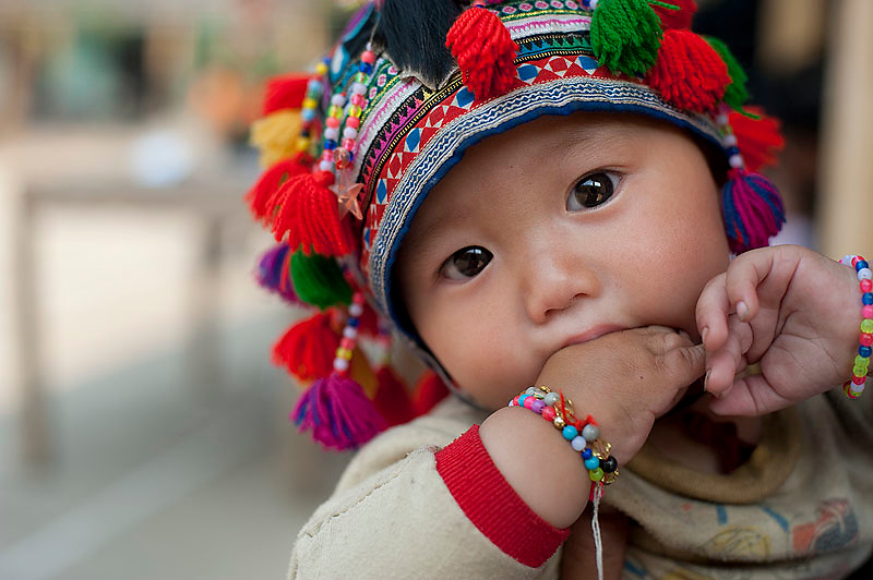 This Hmong baby wears a very bright and colourful hat handmade by the mother.