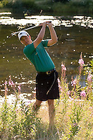 A male golfer chips onto the green out of the rough on Whistler Golf Course, Whistler, BC Canada.