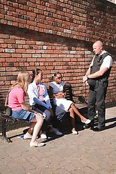 Policeman talking to group of teenage girls.