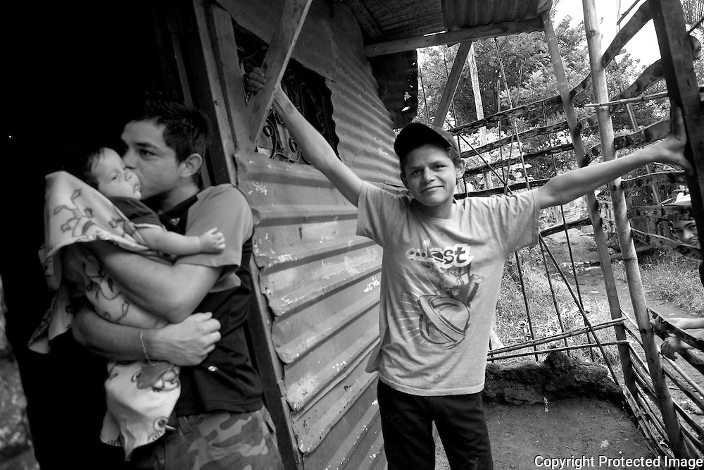 Carlos Tellez Chavez, 17 and his brother Ronald, 22 with his 3 month old son standing outside their home in the slum of Los Pinos in Alajuelita.