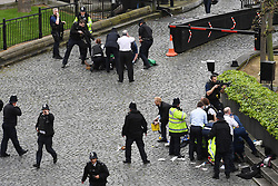 A policeman points a gun at a man on the floor (top) while emergency services attend him and a police officer (bottom) outside the Palace of Westminster, London, after policeman was stabbed and his apparent attacker shot by officers in a major security incident at the Houses of Parliament.