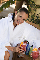 Portrait of woman in bathrobe holding cocktail