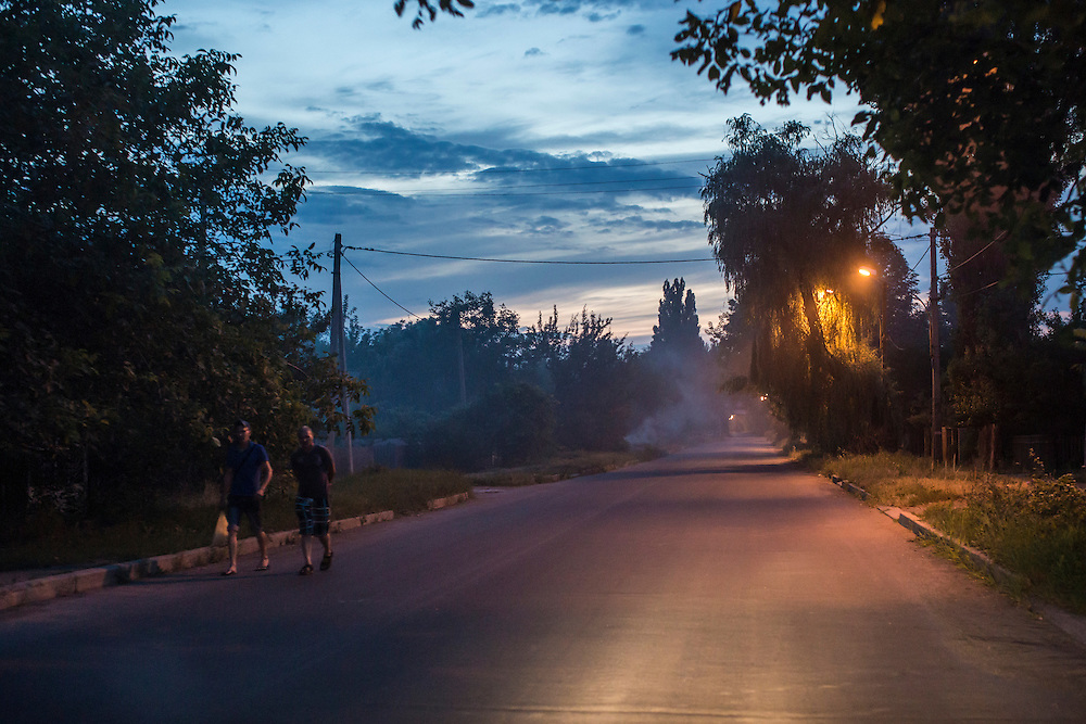AVDIIVKA, UKRAINE - JULY 9, 2016: Two men walk down the street at dusk in Avdiivka, Ukraine. The town is now one of the most active areas of fighting along the line of control between the Ukrainian government and Russian-backed rebels. CREDIT: Brendan Hoffman for The New York Times