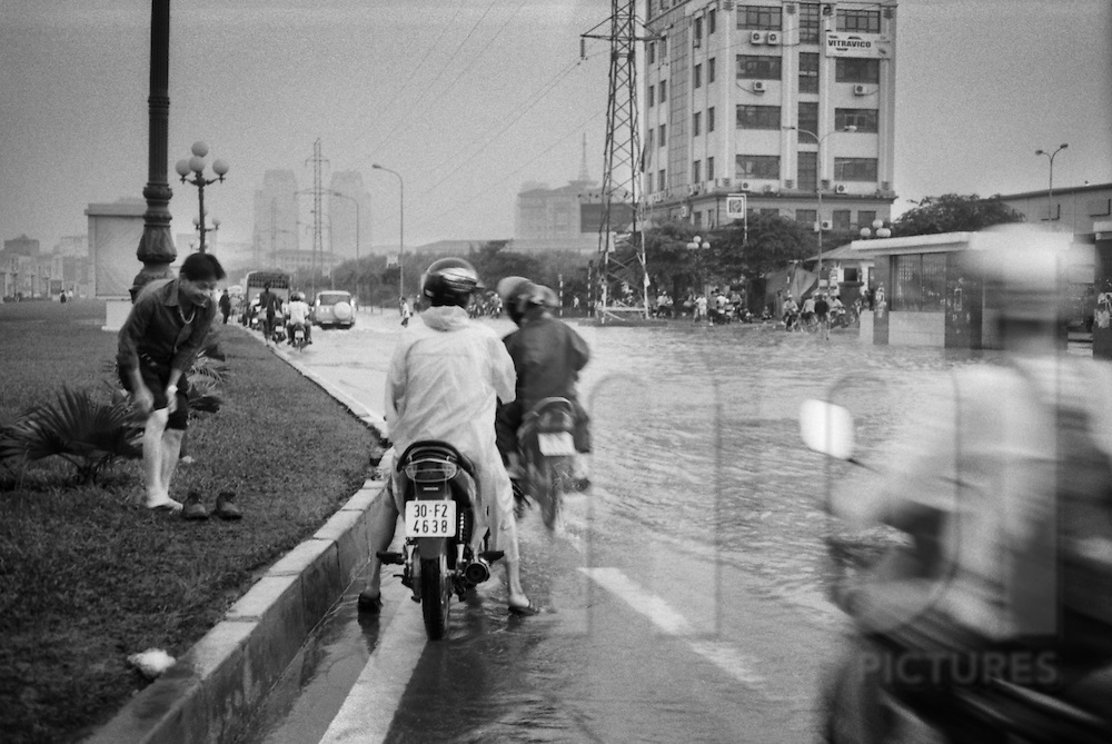 A vietnamese man tries to protect his shoes from the water when riding his bike. The four November 2008, Hanoi, in Vietnam has been hit by its worst floods in 35 years.  Between Friday and Monday, more than 60 centimeters of rain paralyzed the city, causing massive damage and some twenty deaths. Pham Hung.Cau Giay