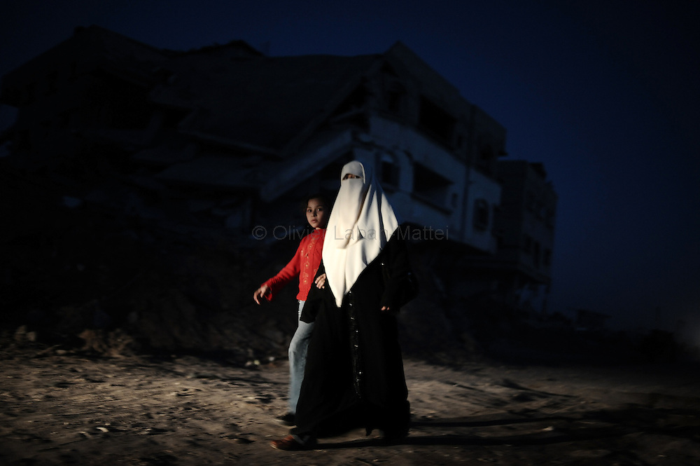 A palestinian woman and a child walk past a destroyed house in the Israeli-bombed Jabalia in the northern Gaza Strip on January 23, 2009. A Hamas delegation from Gaza crossed into Egypt for talks to shore up the ceasefire with Israel which ended a 22-day assault on the coastal strip, a border official said. Israel and Hamas have observed their own ceasefires since January 18 when Israel ended Operation Cast Lead leaving a trail of devastation and 1,330 Palestinians dead, according to doctors. Egypt is trying to secure a durable ceasefire between Israel and Hamas and the reopening of crossings.
