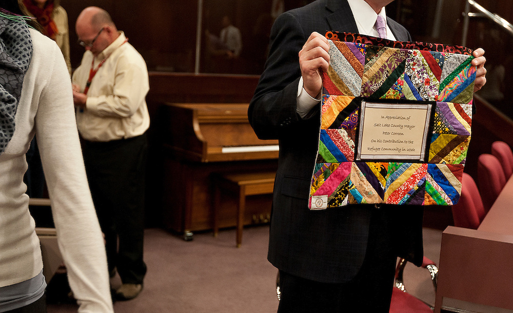 Mayor Peter Corroon holds up a patchwork quilt made in appreciation for his work for the refugee community of Salt Lake at the County Government Center, Tuesday, Dec. 4, 2012.