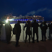 VENICE, ITALY - DECEMBER 18:  Protesters hold a flare and a banner as a cruise ship passes in front of them as they protest against large cruise ships in St Mark's basin on December 18, 2011 in Venice, Italy. Venetians and Environmentalists are opposed tocruise ships, which plough through the shallow Venetian lagoon, damaging the fragile buildings and canal banks.