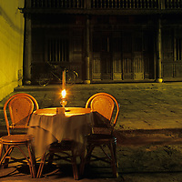 Asia, Vietnam, Hoi An, Lantern at empty restaurant table along street facing Thu Bon River at night