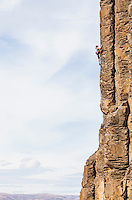A woman climbing a basalt rock cliff in central Washington State, USA.