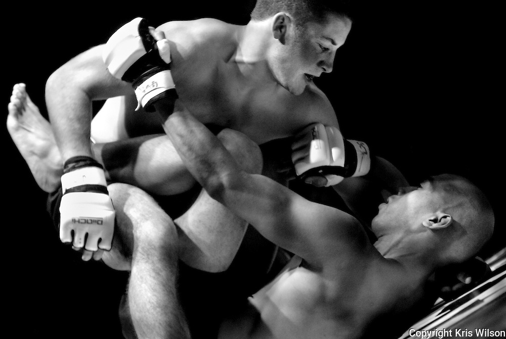 Mixed martial arts fighters struggle to gain a decisive advantage over each other after going to the mat early in their bout during an amateur extreme cage fighting tournament at the Ted Constant Convocation Center on the campus of Old Dominion University in Norfolk, Va.