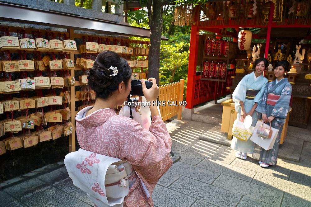 Japanese woman wearing traditional kimono taking photographs at the Kiyomizu Temple.
