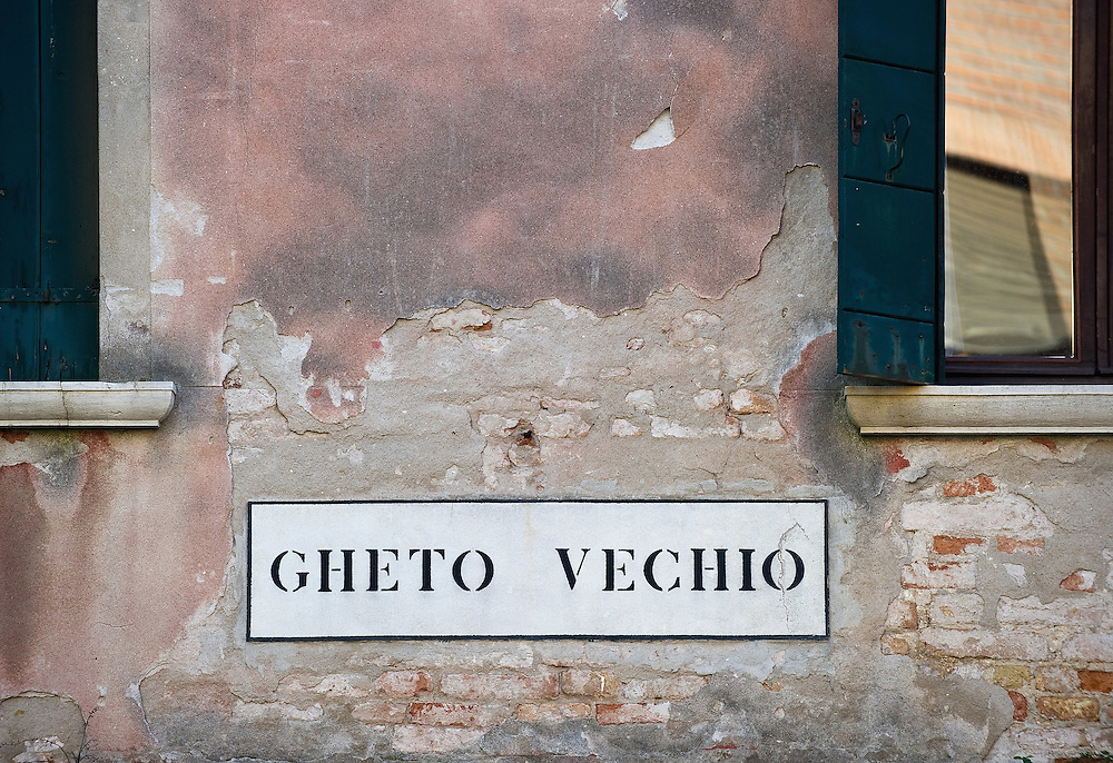 VENICE, ITALY - NOVEMBER 15: A sign displayed on a wall shows the entrance to the Old Ghetto on November 15, 2011 in Venice, Italy. Established in 1516 the Ghetto of Venice was the area were Jews were compelled to live during the Venetian Republic. The English term 'ghetto' is derived from the Venetian term for 'slag' and refers to the refuse left the foundry that was located on the same island. In present times the ghetto is a multi-ethnical area area seen as the cultural heart of the city, but with five synagogues remains the centre of the of Jewish community. .