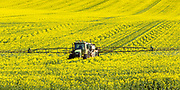 John Deere tractor and sprayer unit spraying field of canola near  Yathella, New South Wales, Australia.
