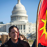 Teko, holds a Mohawk warrior flag, prior to a protest and march from in front of the U.S. Capitol to the EPA, about the North Dakota Access Pipeline, as well as the effort to free Leonard Peltier.  Teko is Huastec, an indigenous people from Mexico, although he lives in DC.  He is part of the organization, DC for Standing Rock, a group organized to support the efforts of the Standing Rock Sioux, in North Dakota. Saturday, December 10, 2016. John Boal Photography