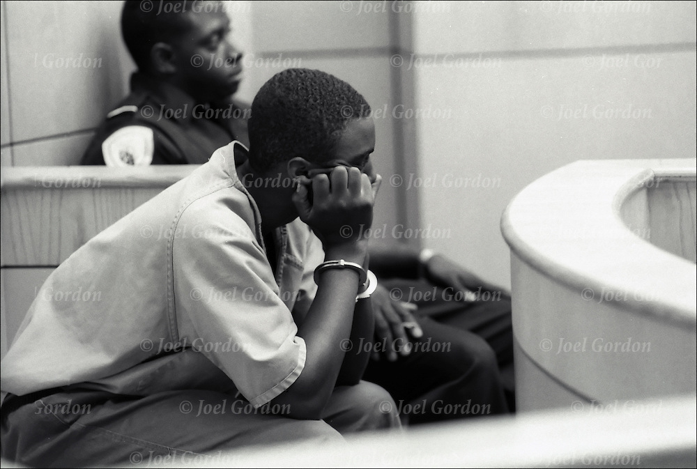 Bored African American juvenile in handcuffed and leg irson sitting waiting for his court hearing in the Juvenile Justice Center, Ninth Judicial Circuit Court in Orlando FL