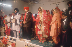 Bride; groom; priest and guests at wedding ceremony in Patiala; Punjab; India,